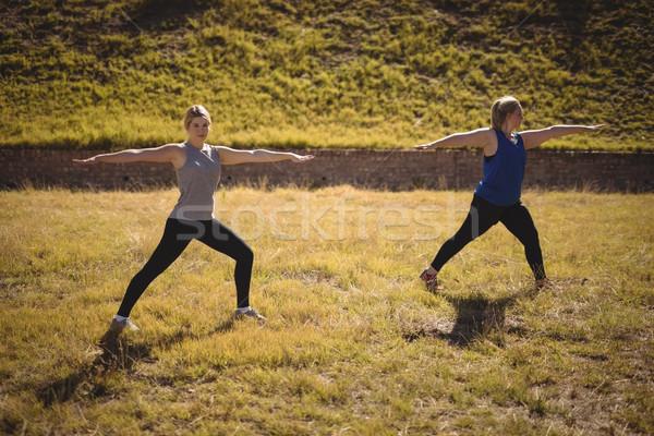 Beautiful women praising yoga during obstacle course Stock photo © wavebreak_media