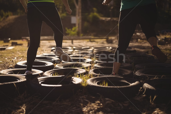 Low section of friends running over tyres during obstacle course Stock photo © wavebreak_media