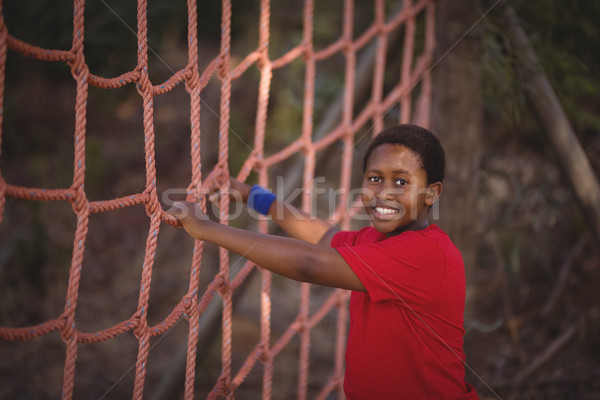Portrait of happy boy standing near net during obstacle course Stock photo © wavebreak_media