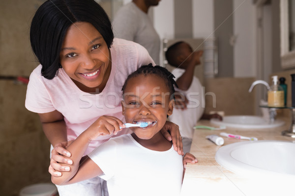 Smiling mother with daughter brushing teeth in bathroom at home Stock photo © wavebreak_media