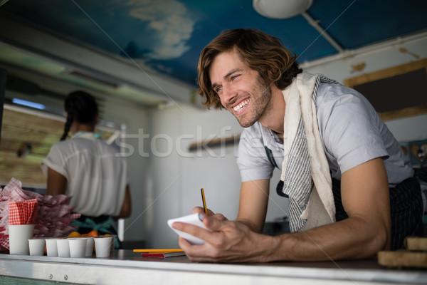 Garçon écrit notepad contre affaires femme Photo stock © wavebreak_media