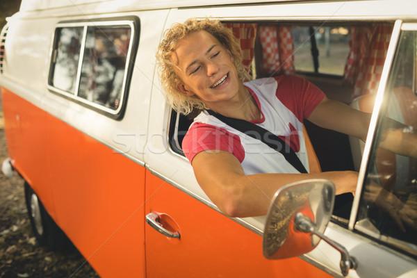 Smiling young man sitting in camper van Stock photo © wavebreak_media