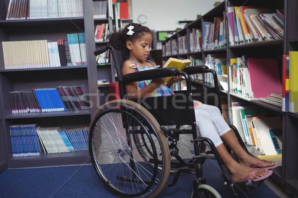 Girl reading book on wheelchair in library Stock photo © wavebreak_media