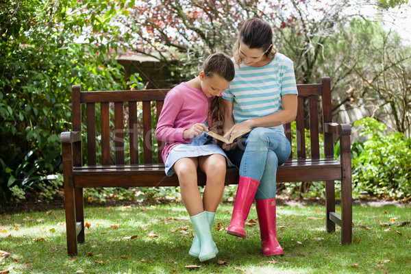 Mother and daughter reading novel while sitting on wooden bench Stock photo © wavebreak_media