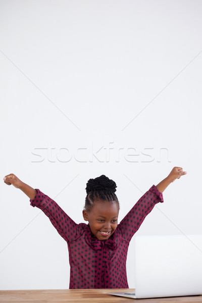 Cheerful businesswoman with arms raised looking at laptop Stock photo © wavebreak_media