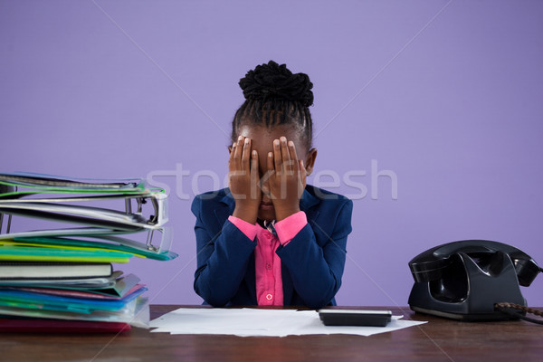 Businesswoman covering eyes while sitting at desk Stock photo © wavebreak_media