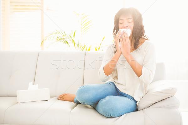 Pretty woman sneezing on couch Stock photo © wavebreak_media