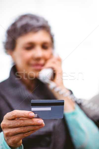 Mature woman holding payment card while talking on telephone Stock photo © wavebreak_media