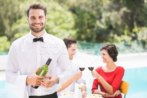 Mosolyog pincér tart borosüveg pár ül Stock fotó © wavebreak_media