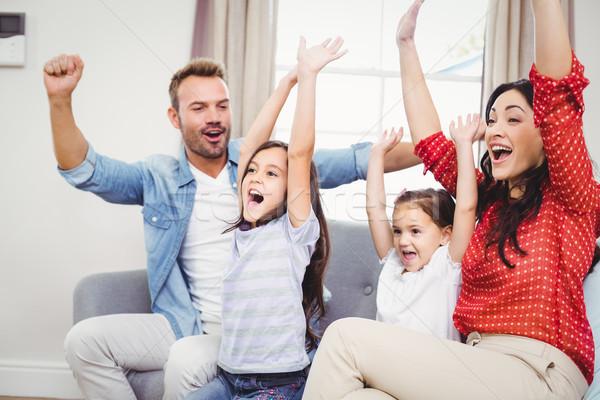 Family cheering while sitting on sofa Stock photo © wavebreak_media