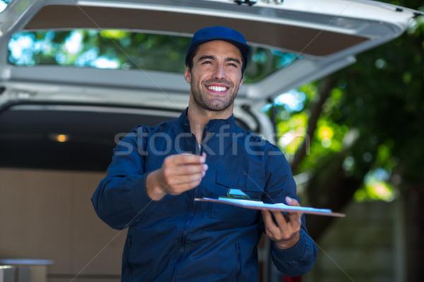 Sonriendo entrega persona portapapeles firma pie Foto stock © wavebreak_media