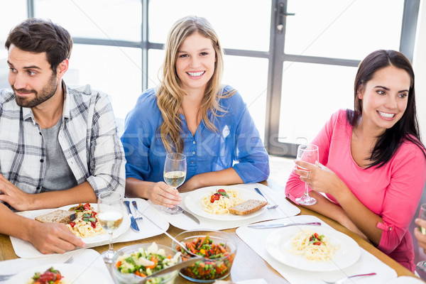 Woman sitting with friends at dinning table Stock photo © wavebreak_media