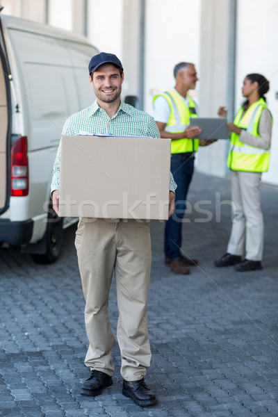 Delivery man is holding a cardboard box and smiling to the camer Stock photo © wavebreak_media