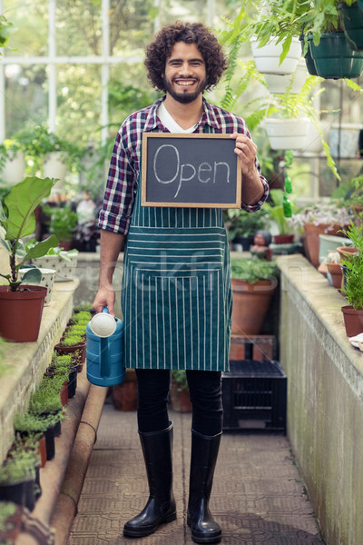 Male gardener holding open sign placard and watering can  Stock photo © wavebreak_media