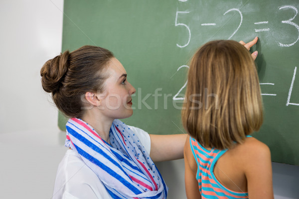 teacher teaching girl on chalkboard in classroom stock photo
