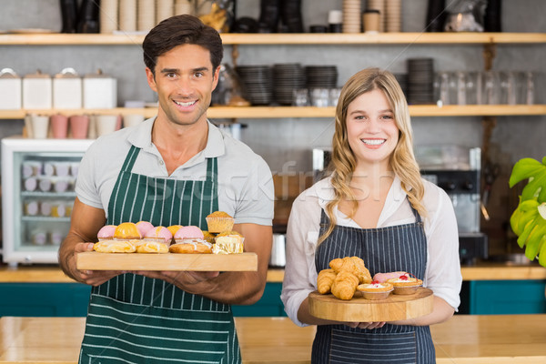 Portrait of waiter and waitress holding a tray of cupcakes Stock photo © wavebreak_media