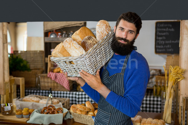 Portrait of male staff carrying wicker basket of breads at counter Stock photo © wavebreak_media