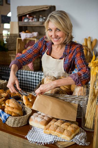 Smiling female staff packing doughnut in paper bag at counter Stock photo © wavebreak_media