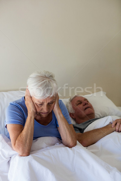 Senior woman getting disturbed with man snoring on bed Stock photo © wavebreak_media