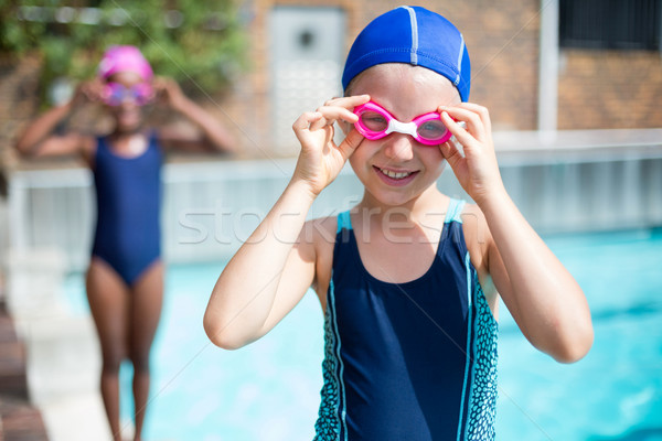 Portrait of smiling girl wearing goggles at poolside Stock photo © wavebreak_media