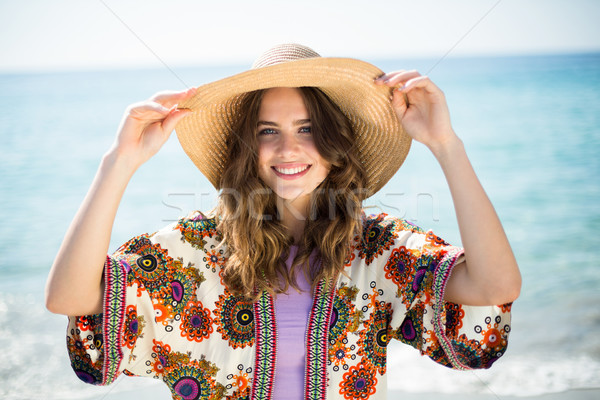 Happy young woman wearing hat while standing at beach Stock photo © wavebreak_media
