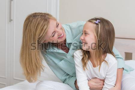 Attentive mother and her daughter drinking coffee lying in bed Stock photo © wavebreak_media