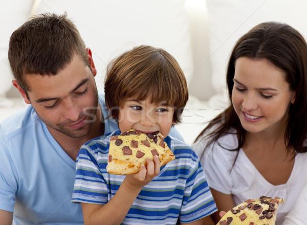 Happy boy eating pizza with ihs parents Stock photo © wavebreak_media