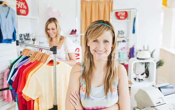 Stock photo: Delighted young woman smiling at the camera doing shopping with her friend standing in a clothes sto