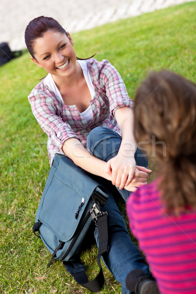 Two female students talking together sitting on the grass at their university campus Stock photo © wavebreak_media