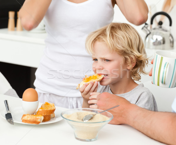 Serious boy eating a toast with marmalade during breakfast with his family Stock photo © wavebreak_media