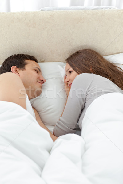 Cute couple looking at each other while relaxing on the bed at home Stock photo © wavebreak_media