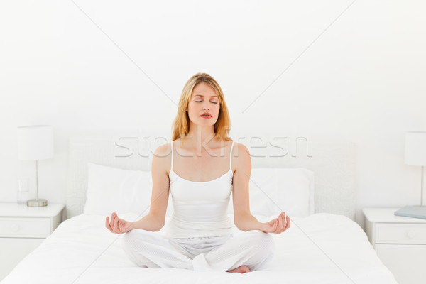 Woman practicing yoga on her bed at home Stock photo © wavebreak_media