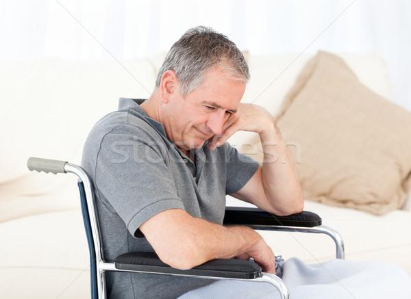 Stock photo: Senior in his wheelchair having a headache at home