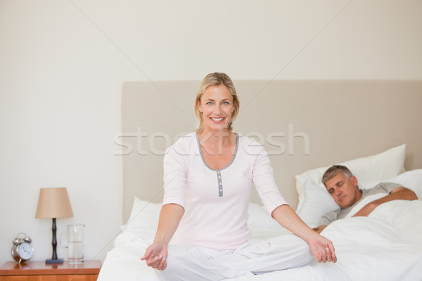 Lovely woman practicing yoga on her bed Stock photo © wavebreak_media