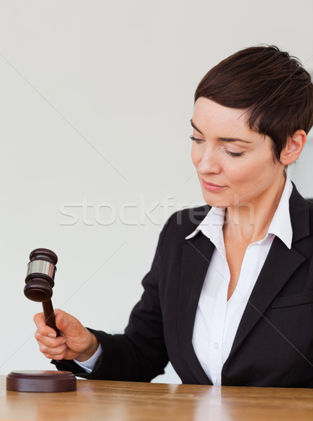 Portrait of a woman knocking a gavel against a white background Stock photo © wavebreak_media