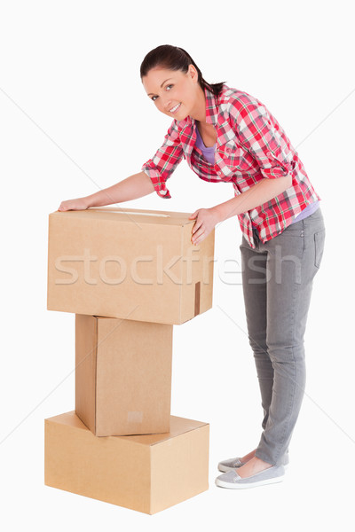 Good looking woman posing with cardboard boxes while standing against a white background Stock photo © wavebreak_media