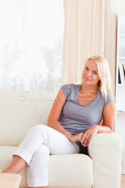 Blonde woman sitting on a sofa in her living room Stock photo © wavebreak_media