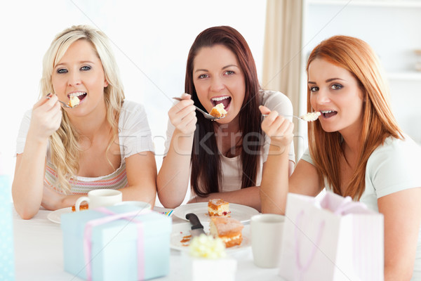Good-looking Women sitting at a table eating a cake in a kitchen Stock photo © wavebreak_media