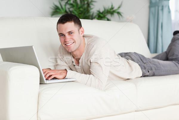 Foto stock: Sonriendo · hombre · sofá · portátil · mirando · cámara