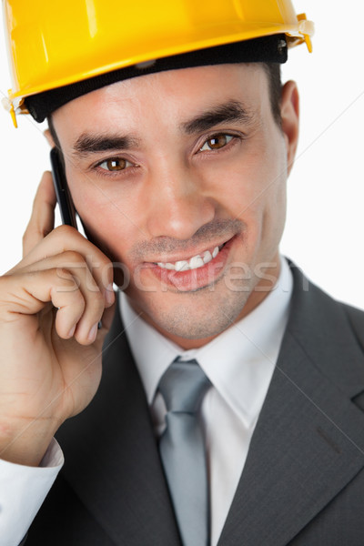 Close up of smiling architect listening to caller against a white background Stock photo © wavebreak_media