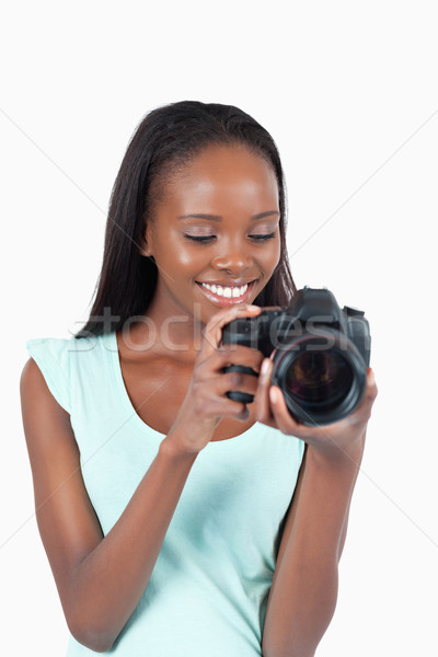 Young photographer taking a look at her cam against a white background Stock photo © wavebreak_media