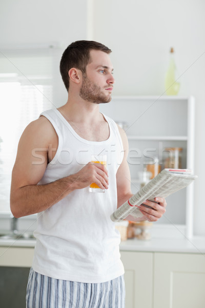 Portrait of a young man drinking orange juice while reading the news in his kitchen Stock photo © wavebreak_media