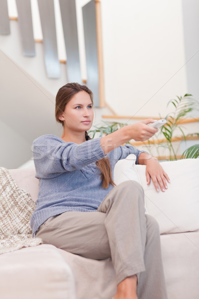 Portrait of a woman switching channel with a remote in her living room Stock photo © wavebreak_media