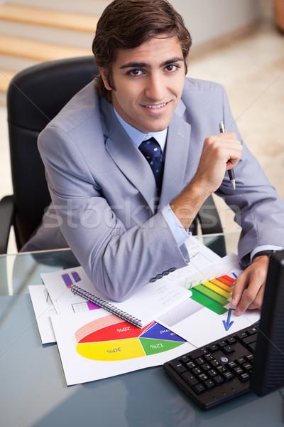 笑みを浮かべて 小さな ビジネスマン 作業 統計 紙 ストックフォト © wavebreak_media