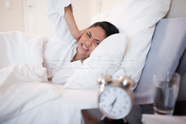 Young woman covering her ears cause of ringing alarm clock Stock photo © wavebreak_media