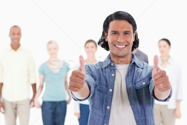 Stock photo: Close-up of a man with his thumbs-up with people behind against white background