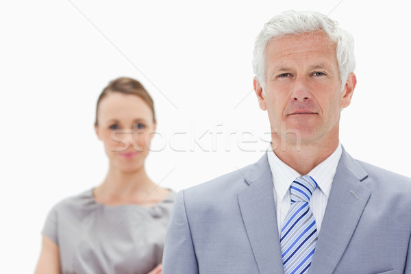 Close-up of a serious white hair businessman with a woman him behind against white background Stock photo © wavebreak_media