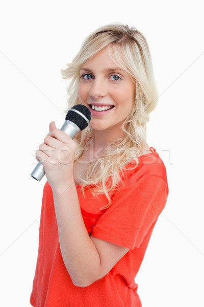 Young attractive and blonde woman smiling while singing in a cordless microphone Stock photo © wavebreak_media