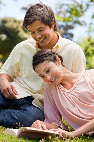 Deux amis souriant lire livre couché Photo stock © wavebreak_media