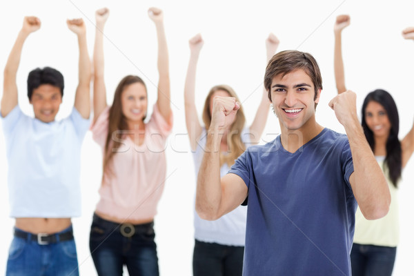 Man clenching his fists with people behind him raising their arms against white background Stock photo © wavebreak_media